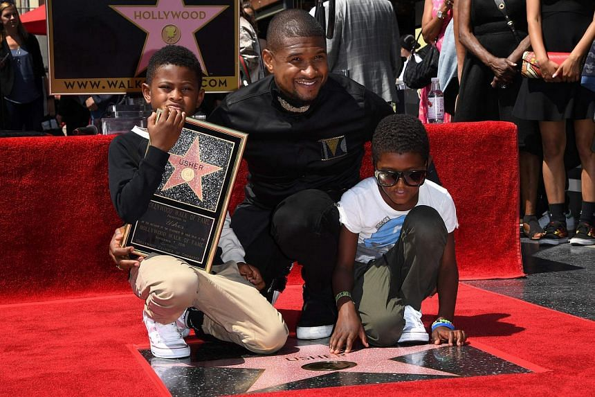 Singer Usher and his sons attend his ceremony after he become the 2,588 entertainer to receive a Hollywood Walk of Fame star in Hollywood, California on Sept 7, 2016.