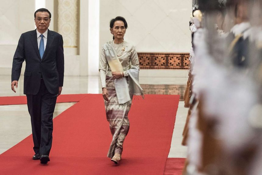 Chinese Premier Li Keqiang and Myanmar State Counsellor Aung San Suu Kyi review a military honour guard during a welcome ceremony at Beijing's Great Hall of the People on Aug 18, 2016.