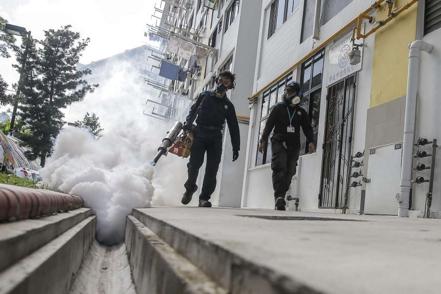 Pest exterminators fumigate a drain canal next to highrise residences in the Aljunied district of Singapore, Aug 31.