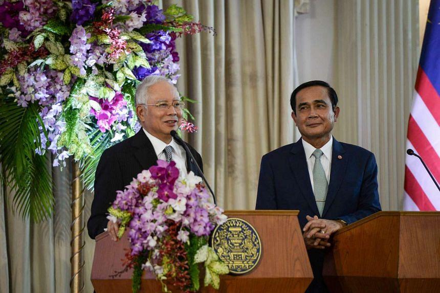 Malaysian Prime Minister Najib Razak(left) and Thai counterpart Prayut Chan-o-cha at a press conference at Government House in Bangkok.