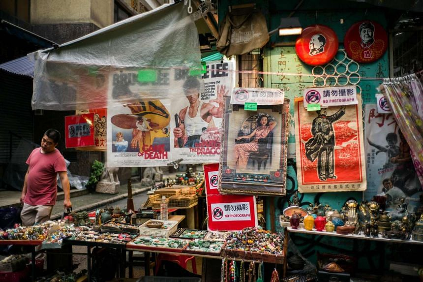 A worker (left) walks past a display of souveniers, including an old propaganda poster depicting Mao Zedong on Sept 9, which marks 40 years since Mao's death in 1976.
