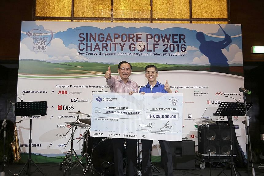 Mr Phillip Tan (far left), chairman of the Community Chest, receiving a cheque from Mr Wong Kim Yin, group chief executive of Singapore Power. The money will go to the Singapore Power Heartware Fund, which supports services for the elderly under the