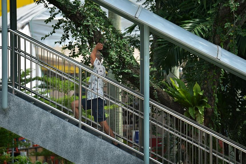 A man doing stretching exercises while walking up an overhead bridge in Toa Payoh Lorong 6 yesterday. With the number of seniors rising even as family support gets weaker, the demand for institutions providing elderly care will grow. However, with se