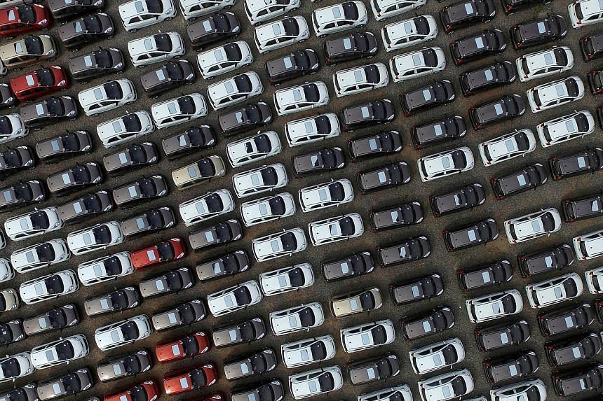 Electric cars seen at a carpark of a factory in China's Hebei province. Both domestic and foreign carmakers have been accused of breaking rules on subsidies for electric and hybrid vehicles. The scandal is a setback to China's goal of achieving full-