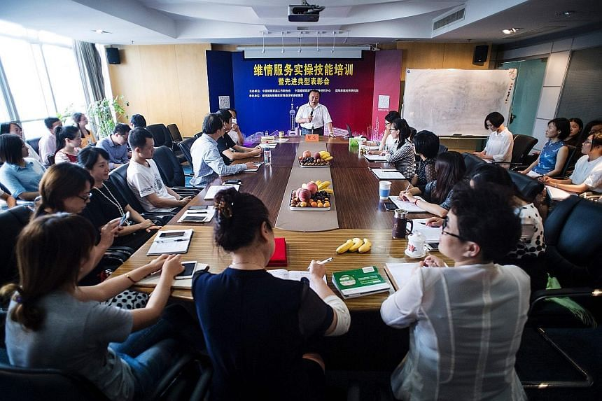 The founder of mistress-hunting firm Weiqing, Mr Shu Xin, holding a meeting at his Shanghai office. His firm's mistress hunters are mostly women and are all psychology, sociology or law graduates.
