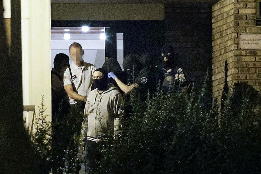 A woman (centre, wearing a hood) being taken out of a building in Boussy-Saint-Antoine, south of Paris, where female suspects - said to have been planning new acts of violence - were arrested. French police investigating Sunday's discovery of a car w