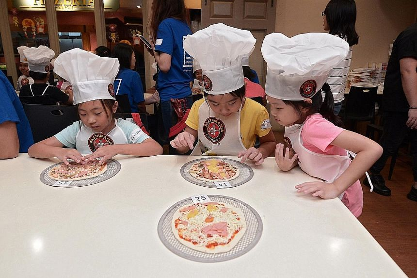 It was a pizza extravaganza for pupils (from left) Celestine Lim, nine, and sisters Elina Kong, nine, and Sririta Kong, seven, yesterday. The three girls were among 34 beneficiaries of The Straits Times School Pocket Money Fund invited to a pizza-mak