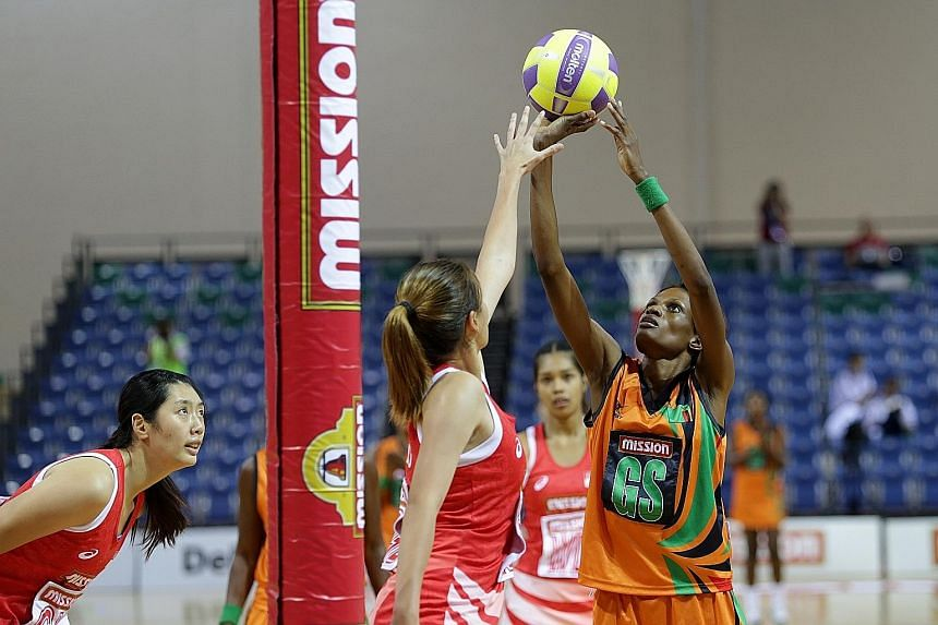 Zambia's Hellen Banda (right) preparing to shoot as Singapore goal defender Shina Teo attempts to block her shot. Zambia won 50-45 and will face Papua New Guinea in the final today.