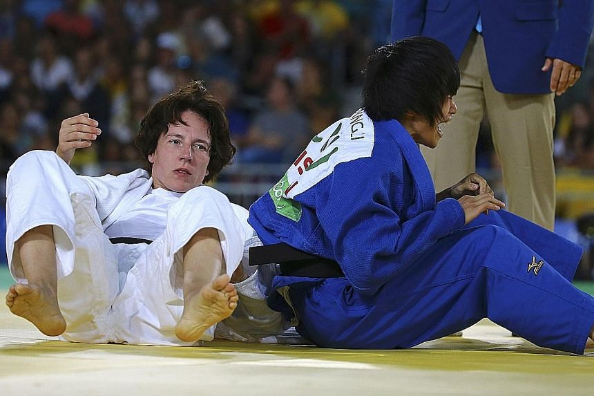 China's Li Liqing (right) is overcome by emotion during the women's judo 48kg final against Germany's defending champion Carmen Brussig.