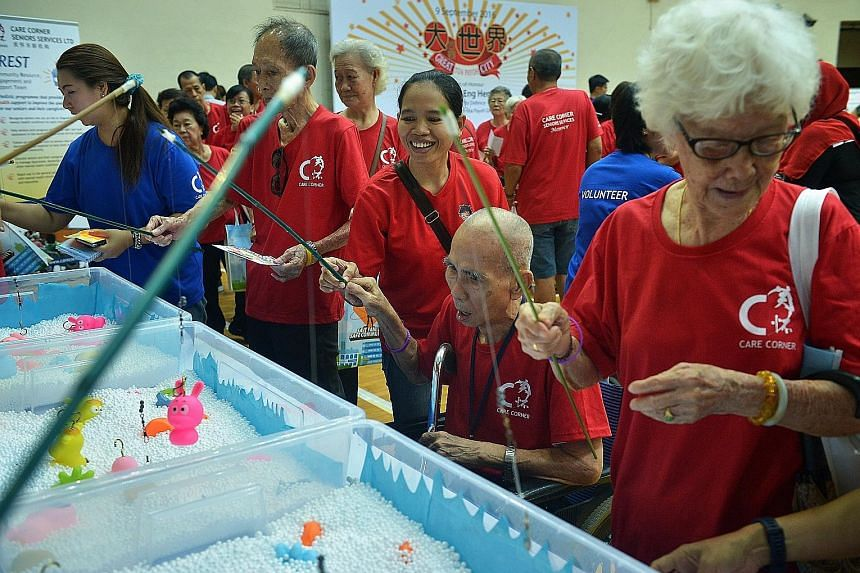 Toa Payoh resident Lim Weng Zuan (second from right), 91, and his helper, Ms Supriatin, trying their hand at a fishing game during a carnival yesterday at the Toa Payoh Sports Hall. Mr Lim was among some 400 seniors who took part in the event organis