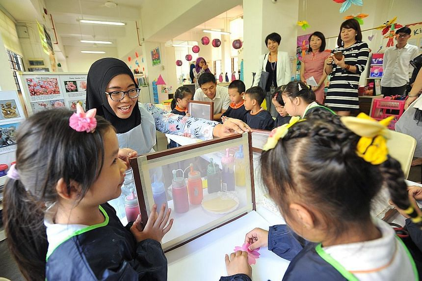 English teacher Nurulhuda Rahmat doing silkscreen printing with her pupils during a visit by Social and Family Development Minister Tan Chuan-Jin (in the background) at My First Skool in Haig Road yesterday. The 29-year-old is in the first batch of t