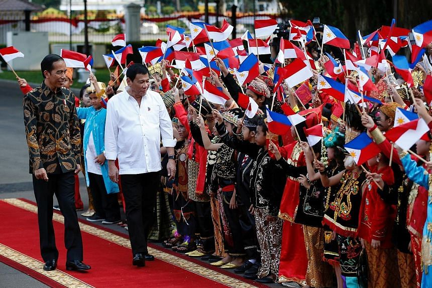 """Mr Duterte (right) being welcomed to the presidential palace in Jakarta yesterday, with Mr Joko beside him. Mr Duterte said their discussion was """"very productive"""" and he was pleased that Indonesia and the Philippines agreed to have more people-to-peo"""
