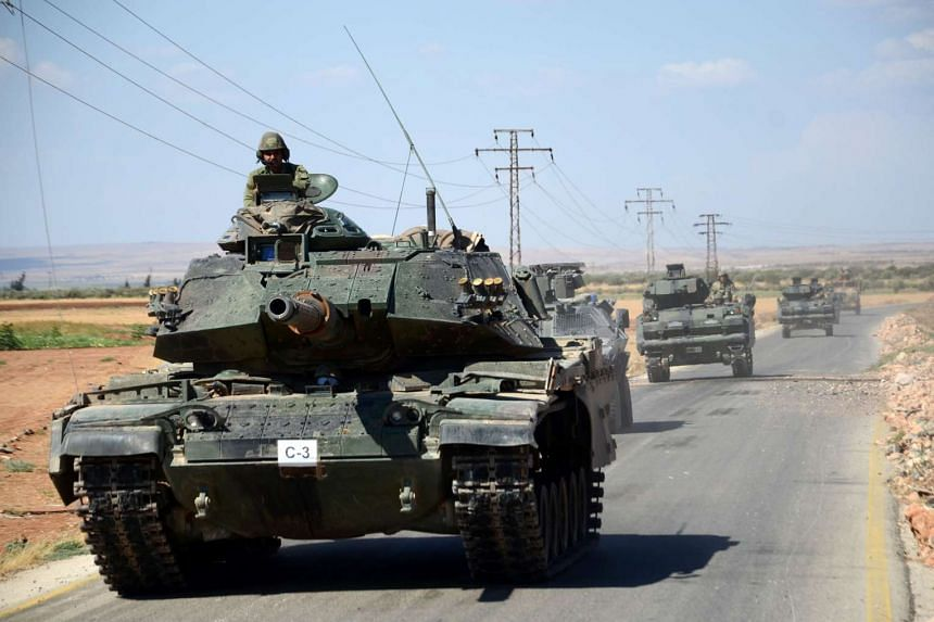 Turkish troops drive their tanks on the road near the Syrian village of al-Waqf on Sept 4, 2016.