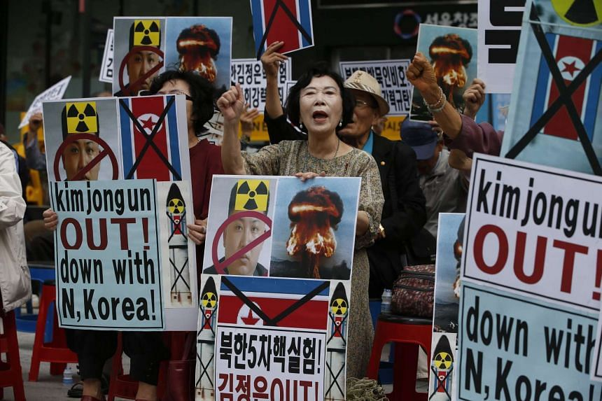 South Korean activists shout slogans as they hold up banners during a rally held to protest against North Korea's fifth Nuclear test on Sept 10, 2016.