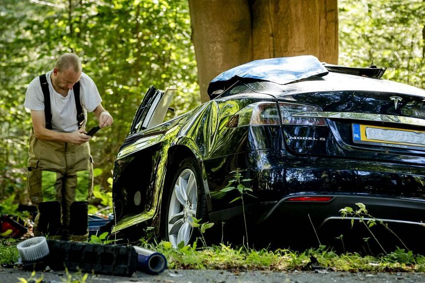 A rescue worker takes a picture around the spot where a Tesla slammed into a tree in Baarn, on Sept 7, 2016.