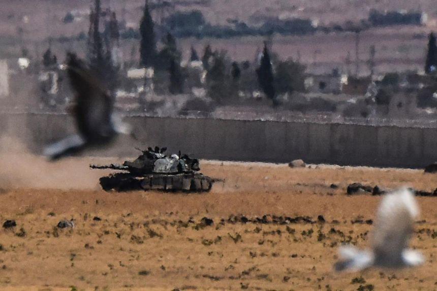 Birds fly near a Turkish tank coming from Syria during clashes between Turkish army and ISIS militants on Sept 4, 2016 at Elbeyli, in the southern region of Kilis.