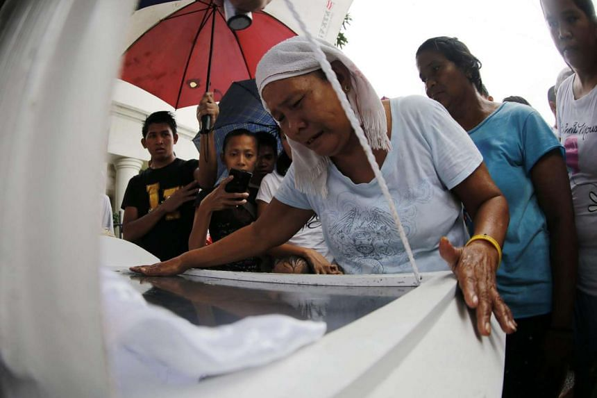 Relatives of a slain alleged drug dealer who was killed during a police operation against illegal drugs, mourning during burial rites at a cemetery in Manila on Sept 4, 2016.