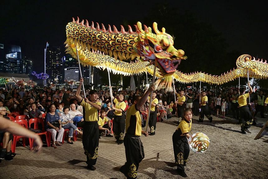 Beneficiaries of voluntary welfare organisations such as Peace-Connect Seniors Activity Centre, the Chinese Development Assistance Council and Transient Workers Count Too enjoying a dragon dance performance by Hong Jie Association at the Esplanade ye