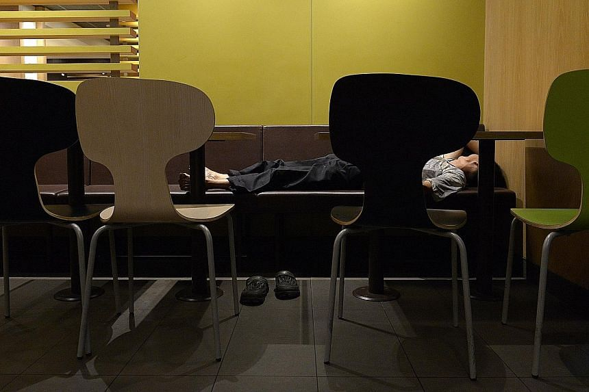 Patrons at a McDonald's outlet in the southern part of Singapore early yesterday morning. Some seek respite in the air- conditioned outlets while others find it hard to sleep at home.