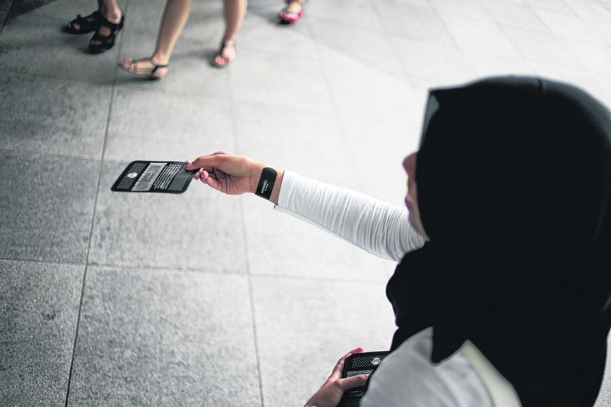 Ms Munirah Abdul Aziz, 21, a student volunteer with Samaritans of Singapore giving out black plasters outside Suntec City yesterday to raise awareness of youth suicide.