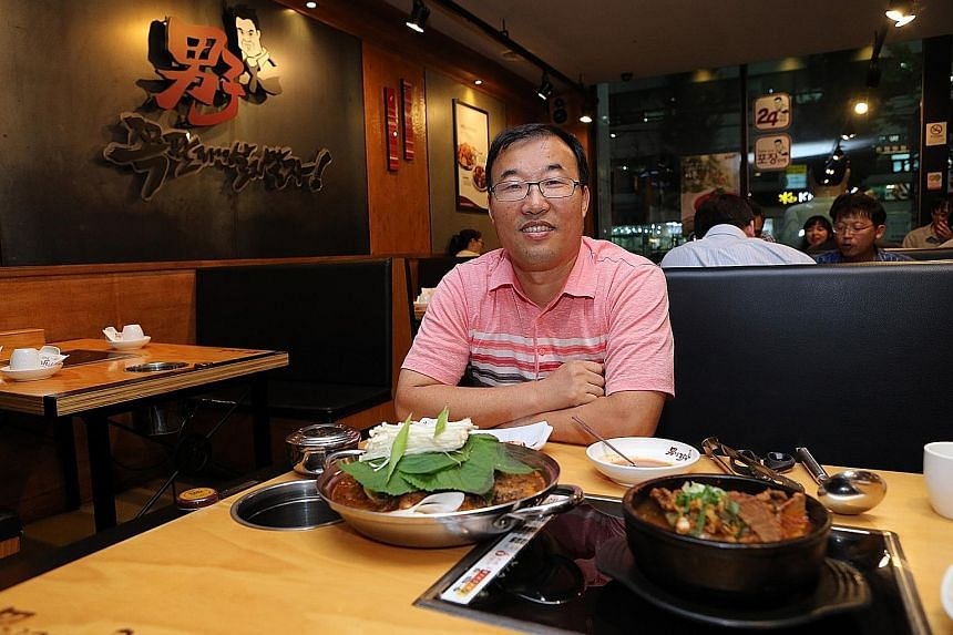 Ms Yoo Hyo Jin sometimes has gimbap (seaweed rice roll) when she lunches solo. Left: Namzatang restaurant owner Jang Sung Bae with a regular serving of spicy pork spine soup and a portion for one (in black pot). Above: Solo diners now make up 30 to 4