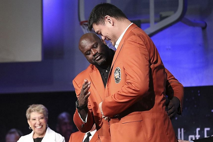 Fellow inductee Shaquille O'Neal helps Yao Ming put on his Hall of Fame jacket during Friday's Basketball Hall of Fame enshrinement ceremony at Springfield Symphony Hall in Massachusetts.