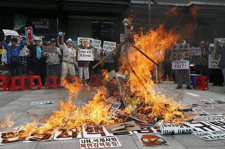 Activists burning an effigy of North Korean leader Kim Jong Un during a rally in Seoul yesterday against the North's fifth nuclear test. South Korea said the nuclear threat from the North is growing and called for tough new sanctions from the UN Secu