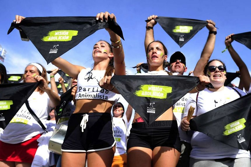 """Demonstrators hold bandannas reading """"Mission abolition"""" during a protest against bullfighting in Madrid on Sept 10, 2016."""
