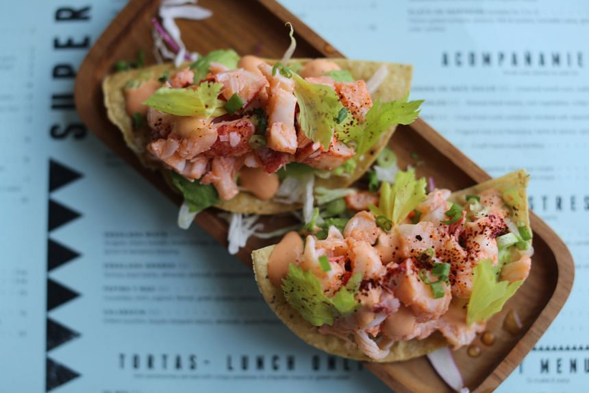 Langosta Tostada ($25+), Maine lobsters with lemon dressing placed on a crisp tostada with avocado, celery hearts and spring onions