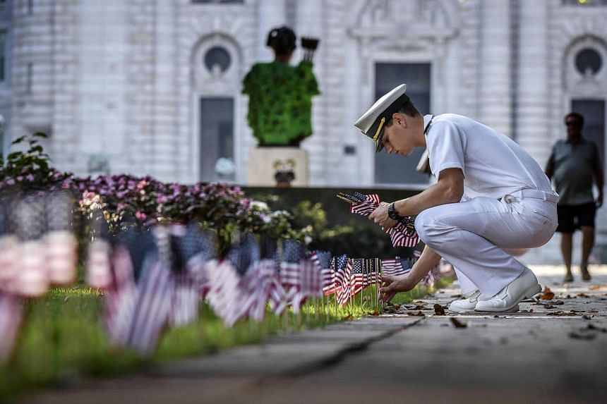 Midshipman Shawn Picciott places one of 2,996 flags on Stribling Walk, representing those lost in 9/11, at the US Naval Academy in Annapolis, Maryland.