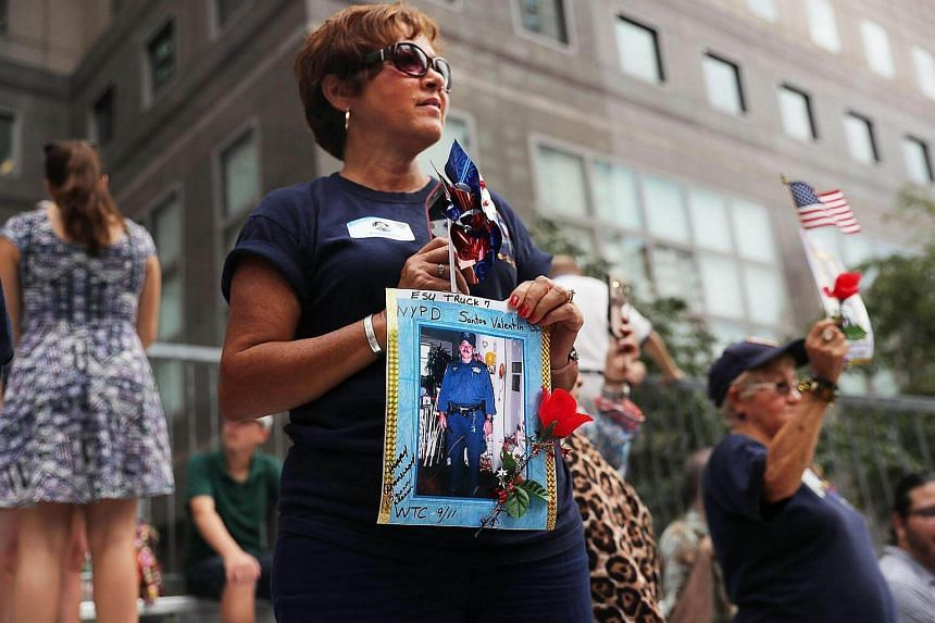 Family members of fallen officers watch a procession in Lower Manhattan to mark the 15th anniversary of the 9/11 attacks and the police officers who were killed during and after the event on Sept 9, 2016 in New York City.
