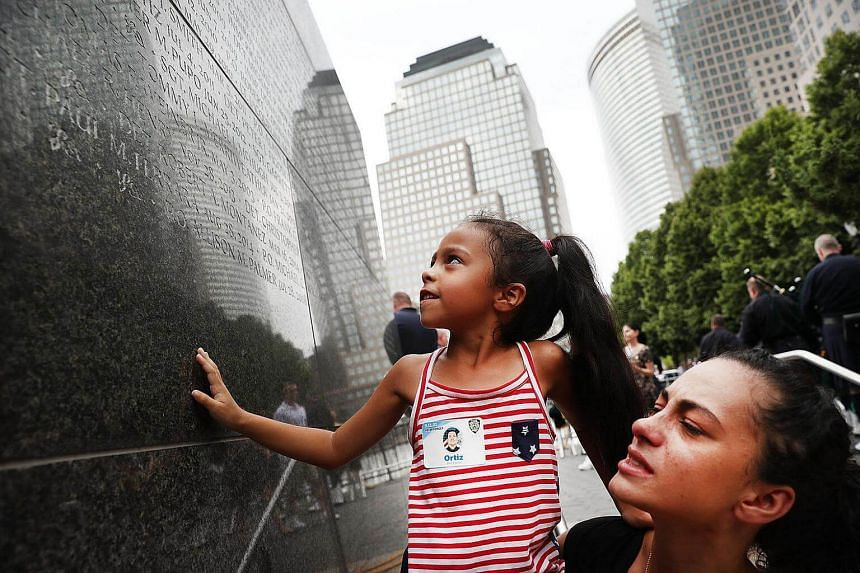 A mother holds up her daughter as she looks for the name of her grandfather fallen New York City Police officer Edwin Ortiz at a wall commemorating fallen officers on Sept 9, 2016 in New York City.