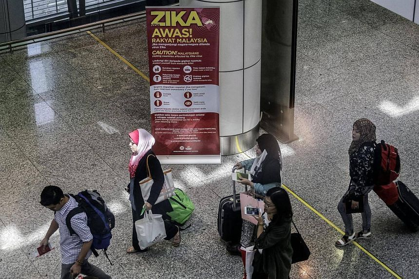 Travellers walking near a travel advisory poster providing information on the Zika virus at Kuala Lumpur International Airport, on Sept 8 2016.