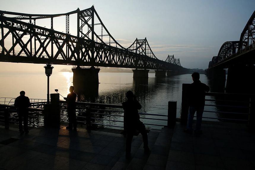 People watch the sunrise behind the bridge over Yalu River that connects China's Dandong, Liaoning province, and North Korea's Sinuiju on Sept 11, 2016.