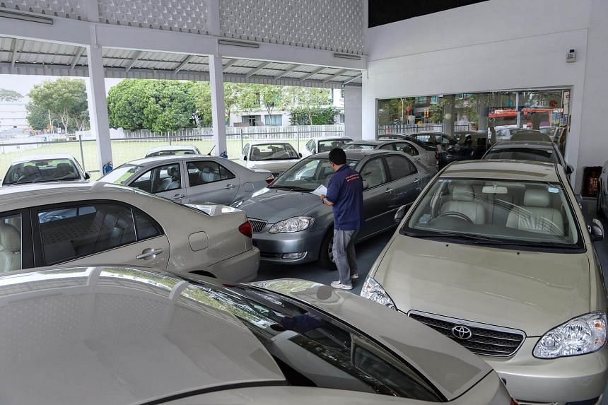 An employee from a rental car company checking the condition of a car among a fleet of cars at its premises on Feb 4.