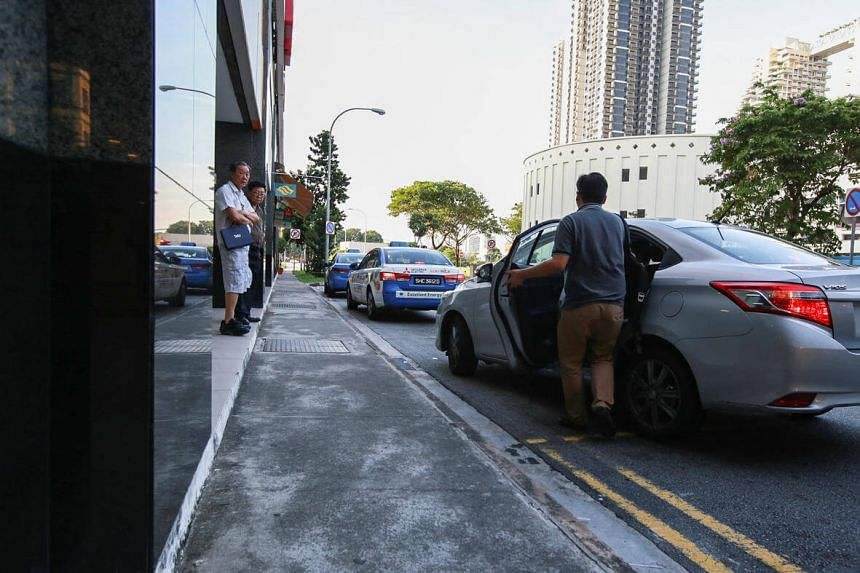 A passenger boarding an Uber car at Bishan Junction 8. Private-hire operators cannot pick up street-hailing customers, who make up 80 per cent of cab trips.