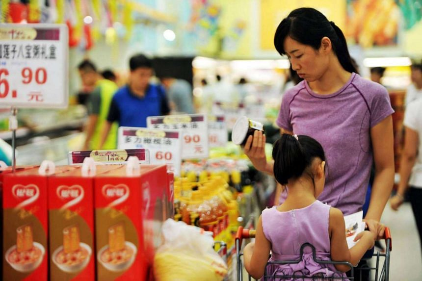 A woman and her child select goods at a supermarket in Qingdao, Shandong province, China on Sept 9, 2016.