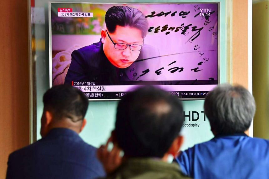 People watch a television news report showing file footage of North Korean leader Kim Jong Un at a railway station in Seoul on Sept 9, 2016.