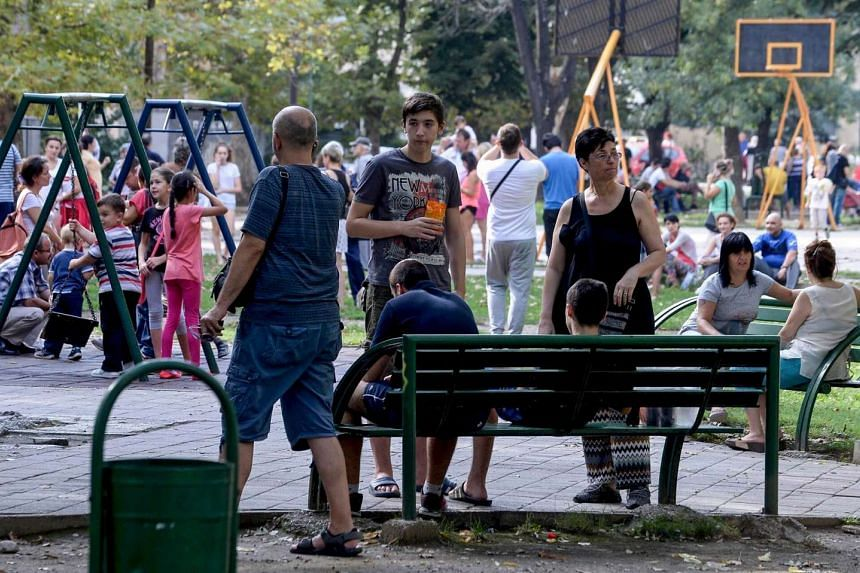 People stay outside on the streets after an earthquake struck near Skopje on Sept 11, 2016.