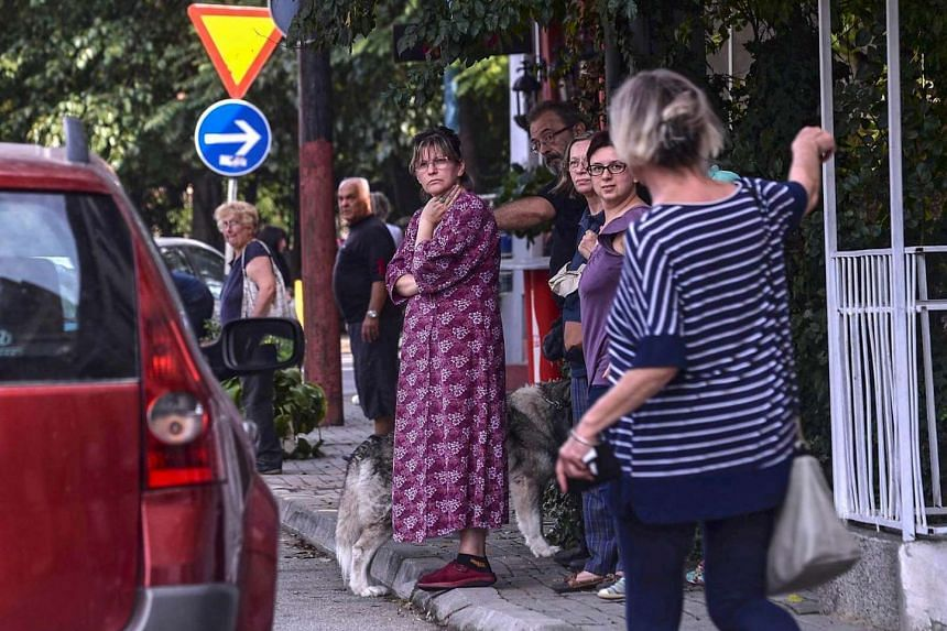 People stand outside on the streets  following a moderate 5.3-magnitude earthquake, preceded by two tremors, near Skopje.