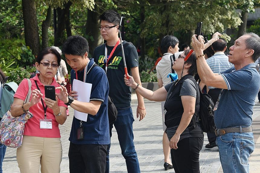 Some seniors getting pointers on how to take selfies and other photos with their smartphones at yesterday's event organised by Singtel and Chinese evening dailies Shin Min Daily News and Lianhe Wanbao.