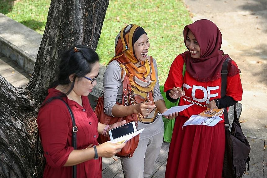 Domestic worker Endang Wiyanti (at right), who is volunteering with the Centre for Domestic Employees, giving out brochures yesterday to fellow domestic workers Sofiah Supridi (centre) and Sumiri.