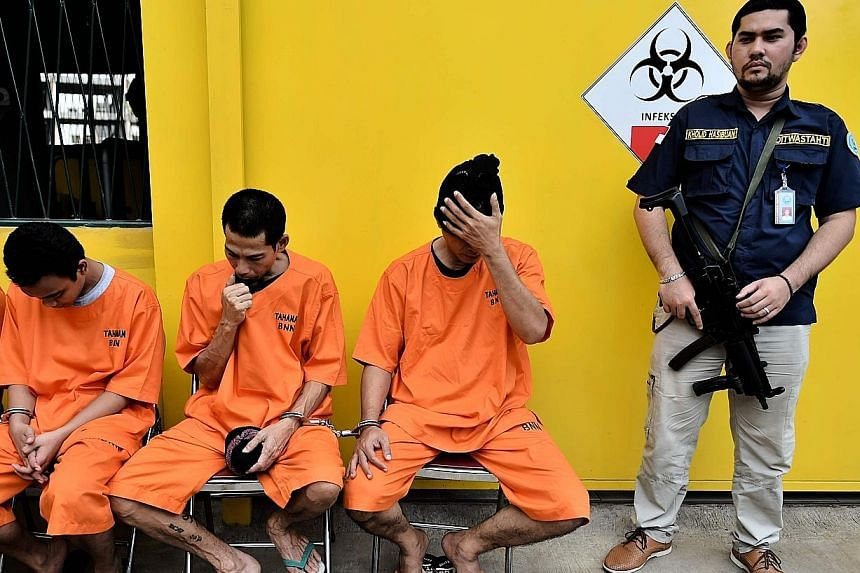"""Indonesian police with foreign and local drug traffickers in Jakarta last week. While the US has begun a bid to roll back the """"war on drugs"""", governments in Asia are largely doing the opposite and adopting hardline anti-drug policies."""