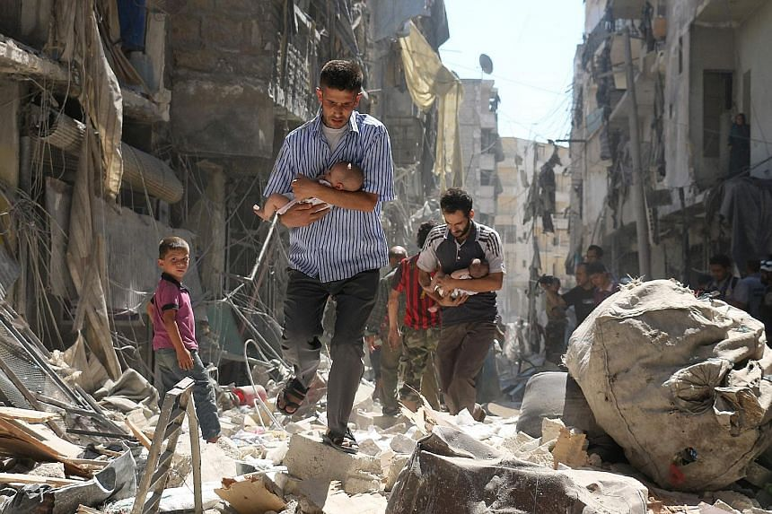 Syrian men protecting babies while making their way through the rubble of destroyed buildings following a reported air strike on the rebel-held Salihin neighbourhood in the northern city of Aleppo yesterday. Even as Syrian rebels and world powers thr