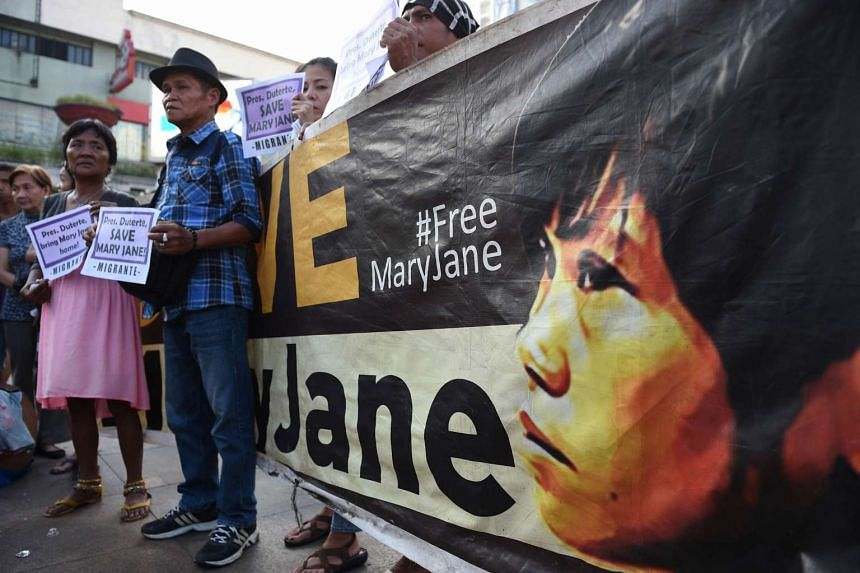 Cesar (second from left) and Celia Veloso (left), parents of Filipina drug convict facing execution in Indonesia, hold a candle light vigil in front of Quiapo church in Manila on Sept 8, 2016.