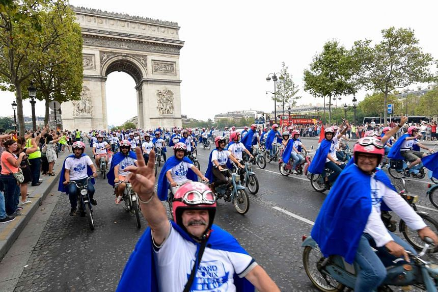 Around 700 entrepreneurs ride their old blue mopeds near the Arc de Triomphe in Paris on Sunday (Sept 11).