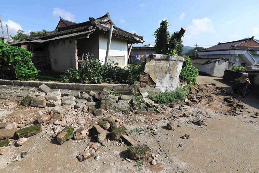 An elderly woman in front of her destroyed house in Gyeongju on Sept 13, 2016.