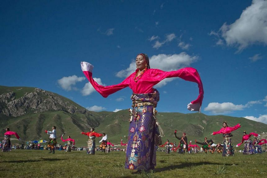 Ethnic Tibetans dancing at a local government sponsored festival in Yushu, Qinghai province, on July 25, 2016.