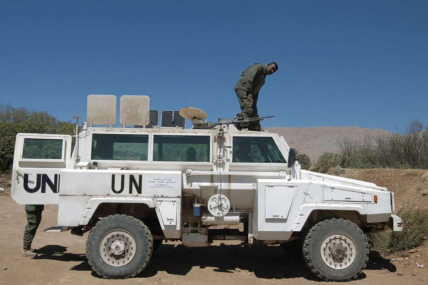 A UN peacekeeper monitors the border with Syria near the village of Majdal Shams in the Israeli-occupied sector of the Golan Heights on Sept 13, 2016.