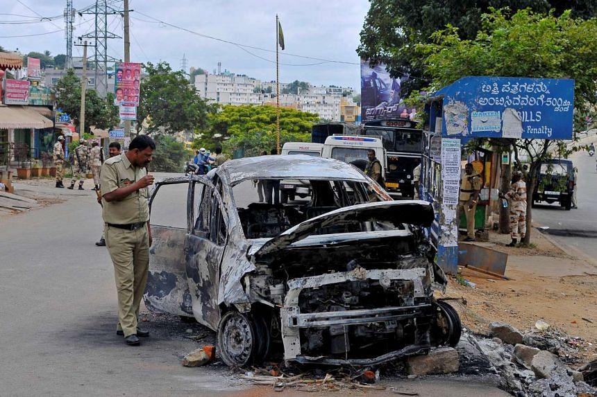A police officer inspects the remains of a car that was set ablaze during violent protests in Bengaluru on Sept 13, 2016.